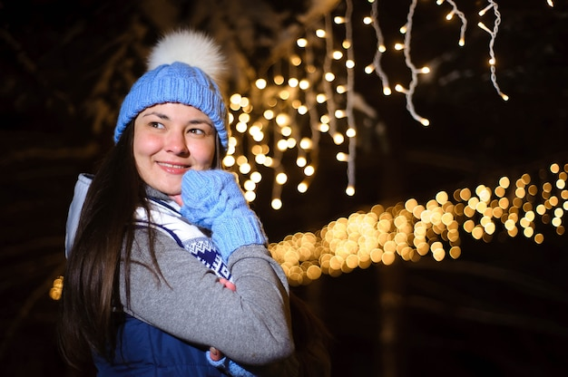 Street portrait of smiling beautiful young woman on the festive christmas fair