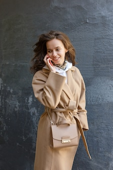 Street portrait of young smiling woman wearing beige coat using cell phone