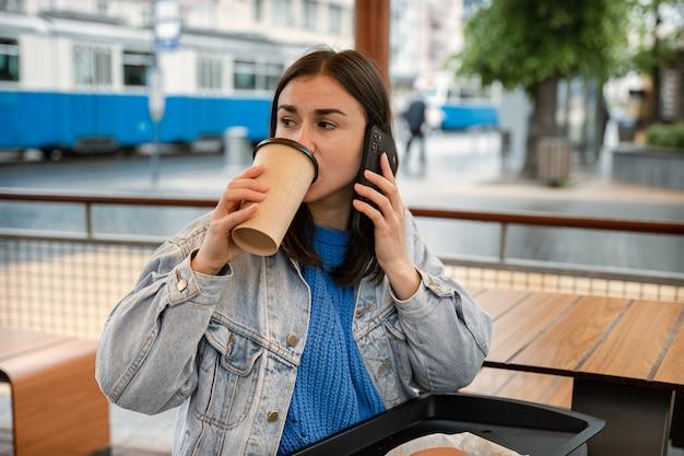 Ritratto di strada di una giovane donna che beve caffè, parla al telefono e aspetta qualcuno.