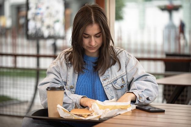Ritratto di strada di una giovane donna con fast food sulla terrazza estiva di un caffè