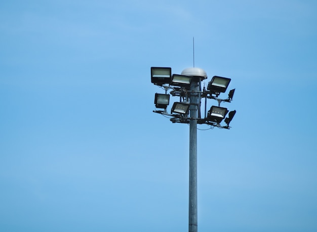 Street public luminaire with lighting pole against a blue sky