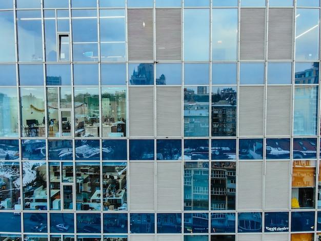 Riflessione della via sulla facciata d'acciaio di vetro della costruzione