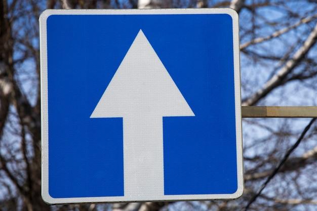 青い正方形の道路標識の白い矢印。一方通行。交通規則。高品質の写真