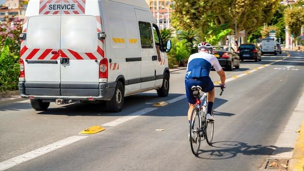 町の街並み。フランス、カンヌの移動中の車とサイクリストのいる道路
