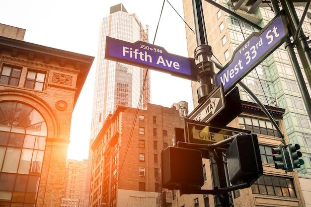 뉴욕시 해질녘 5번가 및 웨스트 33번가의 거리 표지판 - 맨해튼 시내의 도시 개념 및 도로 방향 - 따뜻하고 극적인 필터링된 미국의 세계적으로 유명한 수도 목적지