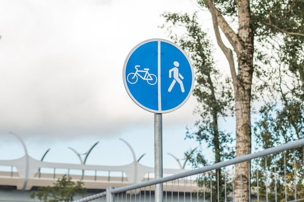 Street sign for pedestrians and cyclists on road in the park