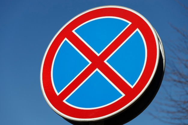 Дорожный знак две пересекающиеся функции на синем фоне. запрет остановки движения. фото высокого качества