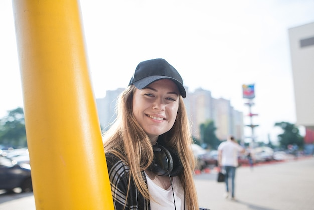 Street smiling stylish girl in casual clothing and headphones in the background of urban landscape