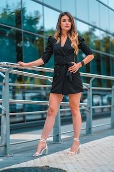 Уличный стиль, молодая кавказская блондинка предприниматель в черном стеклянном здании, где она работает. я бы посмотрел в камеру, прежде чем идти на работу