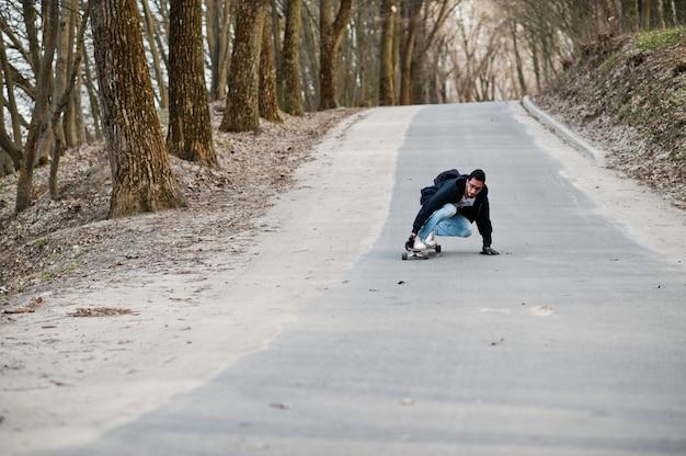 Уличный стиль арабского человека в очках с longboard longboarding вниз по дороге.