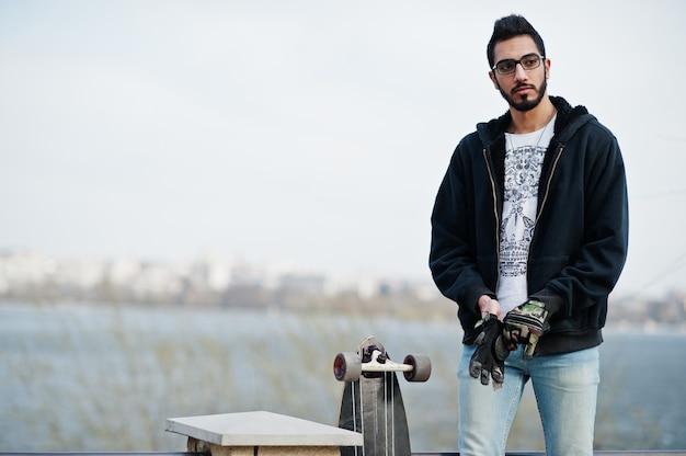 Человек уличного стиля арабский в eyeglasses с longboard представленный против реки.