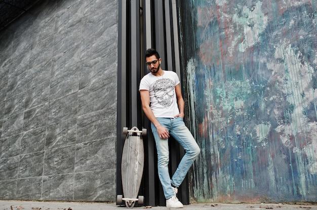Уличный стиль арабских человек в очках с longboard ставил.