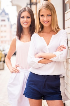 스트리트 스타일의 미녀. 야외에서 서로 가까이 서 있는 동안 카메라를 보며 웃고 있는 두 명의 아름다운 젊은 잘 차려입은 여성