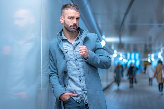 ストリートスタイル、灰色のアメリカのジャケットを着て地下鉄のトンネルで若い白人ブルネットの国際的な肖像画