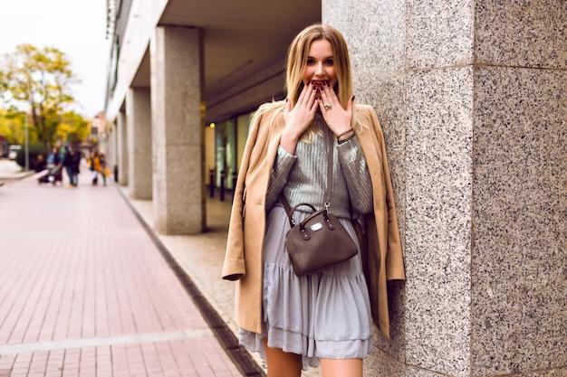 エレガントなグラマーブロンドの女性がショッピングセンター、エレガントなドレスセーター、カシミヤコート、トーンの色、春の時間の近くのヨーロッパのストリートでポーズのストリートスタイルのファッションの肖像画。