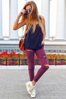 Il ritratto di moda street style di giovane donna sexy in scarpe da ginnastica con tacco di jeans pazzi, ha i capelli biondi alla moda.