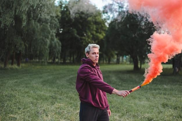 Человек уличного стиля в толстовке с капюшоном держит сигнальную ракету с красной дымовой гранатой.