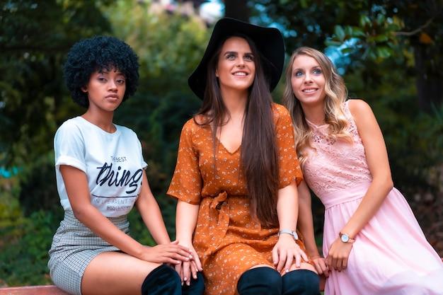 ストリートスタイル。秋の公園に座っている3人の友人、ブロンド、ブルネット、アフロの髪を持つラテンの女の子