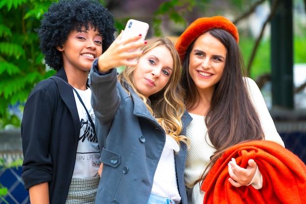 ストリートスタイル。街で自撮りをしている3人の友人、ブロンド、ブルネット、アフロの髪を持つラテンの女の子