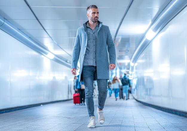 ストリートスタイル、灰色のアメリカンジャケットを着て地下鉄のトンネルで若い白人ブルネット