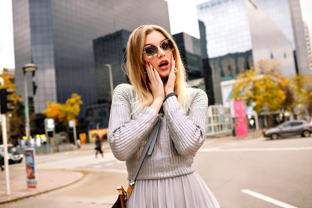 Street stylish portrait of blonde woman wearing glamour grey outfit at put hand to her sunglasses, business center area. surprised face.