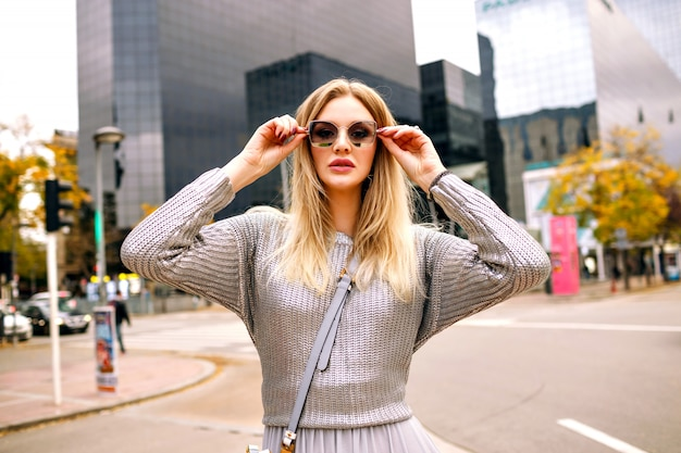 Street stylish portrait of blonde woman wearing glamour grey outfit at put hand to her sunglasses, business center area.