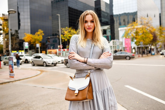 Street stylish portrait of blonde woman wearing glamour grey outfit