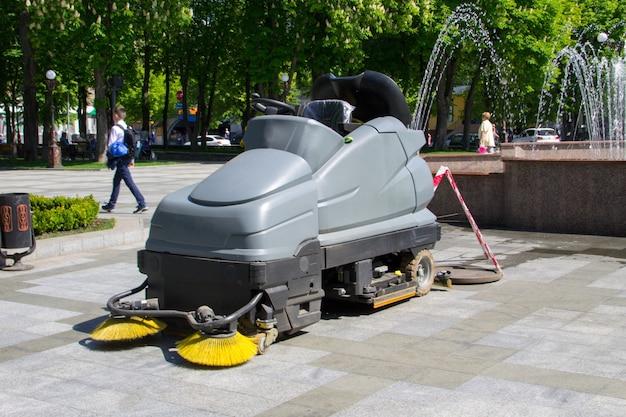 Подметально-уборочная машина чистит дорожки в парке