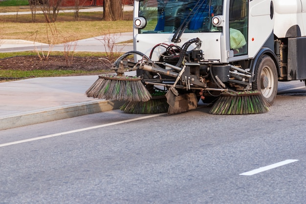 Подметально-уборочная машина работает на асфальтовой дороге