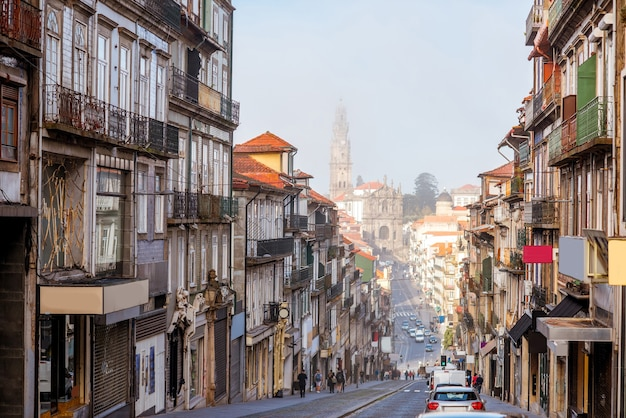Просмотр улиц с церковью клириков туманным утром в городе порту, португалия