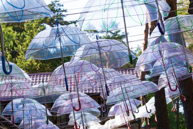 Street on which many transparent umbrellas hang against the sky.