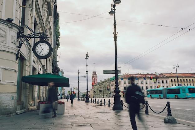 早朝に時計と歩行者がいる通り。水平方向の画像。