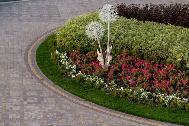 돌 타일로 포장 된 공원의 꽃과 산책로가있는 거리
