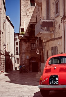 Street with an old red car