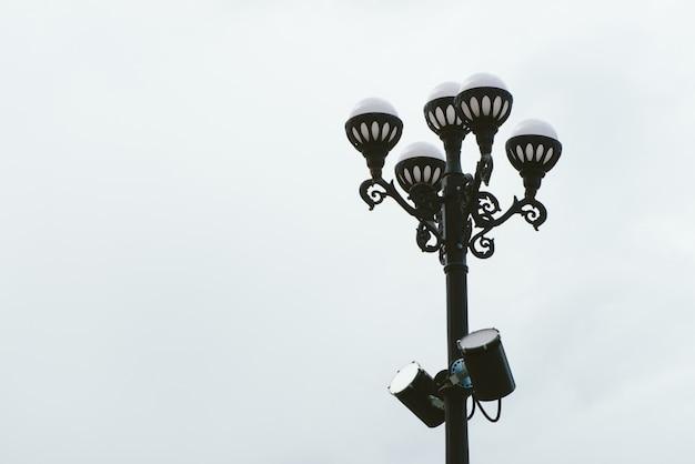 Уличный светильник с пятью сферическими лампами на черный старинный столб на фоне облачного неба. уличный свет в пасмурную погоду с копией пространства. уличные фонари крупным планом. два прожектора на шесте.