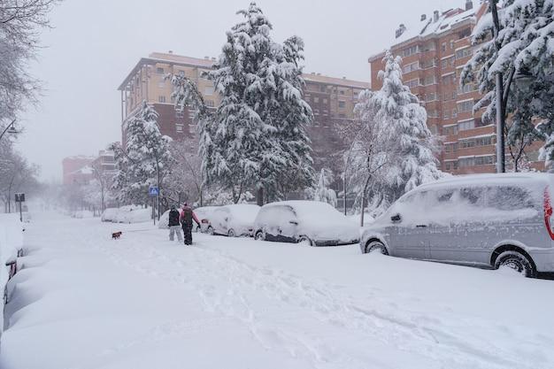 스페인 마드리드에서 떨어지는 눈보라 filomena로 인해 거리와 건물이 낮에 눈으로 덮여 있습니다. 눈 속에서 걷는 사람들. 스페인