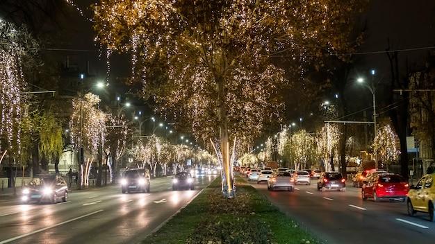 Уличный вид города ночью, автомобили, движущиеся по дороге, много рождественского освещения в бухаресте, румыния