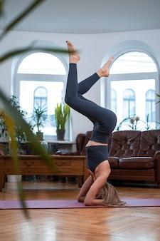 自宅での体力とヨガの練習。優雅な若いスポーツウーマンは、モダンなアパートで上げられた足で彼女の手に立って運動します。
