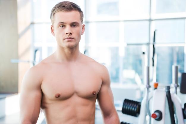 強さと男らしさ。ジムに立っている間カメラを見て自信を持って若い筋肉の男