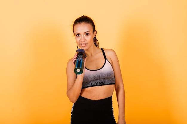 힘과 동기. 노란색 배경 스튜디오에서 운동하는 스포츠 의류에 젊고 슬림 한 아프리카 여자의 전체 길이