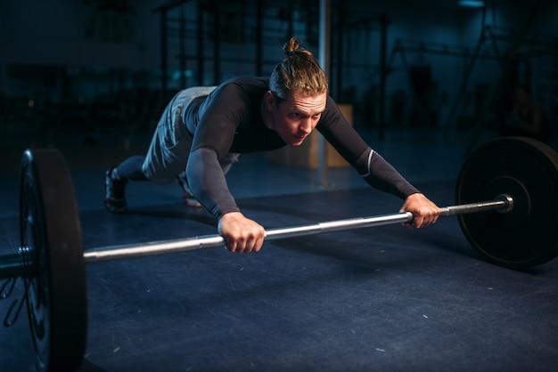 Силовик на тренировке, отжимания со штангой в тренажерном зале.