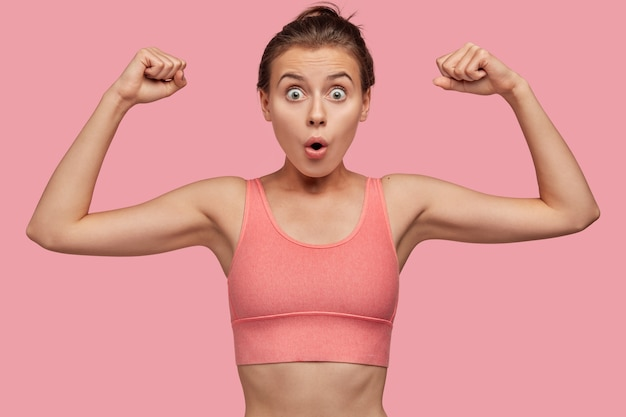 Strength and feminism concept. surprised young european sportswoman in pink casual top shows hand muscles