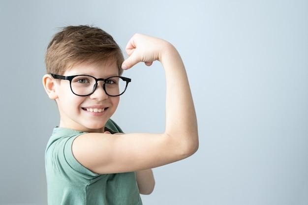 녹색 티셔츠와 안경에 힘 웃는 소년 잠겨있는 그의 머리를 긁적