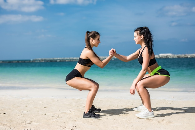 Strength in teamwork. two young attractive women athletes exercise doing squats on the beach near beach