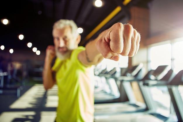 男性に焦点を当てたジムでワークアウトしながら、筋力トレーニングはスポーツウェアボクシングの成熟した男性に焦点を当てた