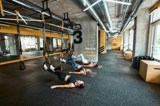 피트니스 trx와 함께 운동하는 운동복을 입은 3명의 젊은 백인 운동 여성의 근력 훈련