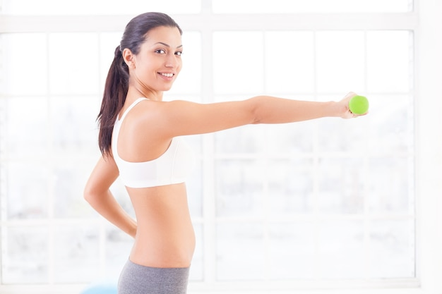 Strengthening her muscles. side view of beautiful young indian woman stretching out hand with dumbbell and smiling at camera