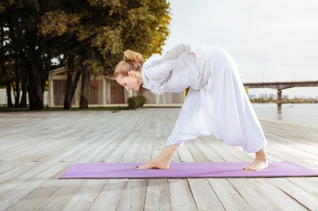 ヨガで筋肉を強化します。ビーチで屋外ヨガを行う若い女性