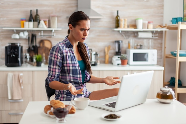 Stresed woman using laptop in kitchen during breakfast with cup of green tea