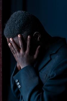 Стресс африканский мужчина в темной комнате, сдержанный стиль